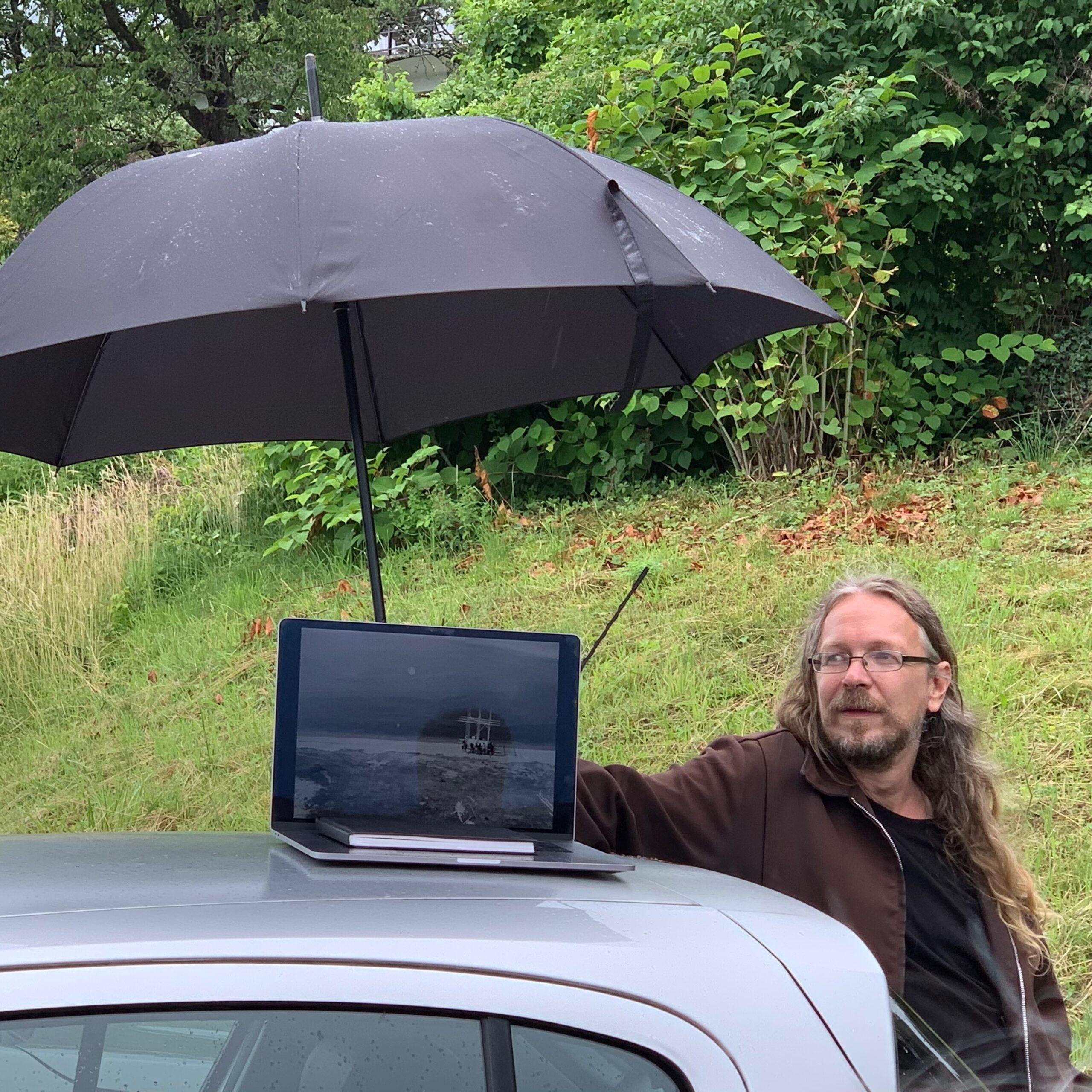 Matthieu Jaccard abrite d'un parapluie la présentation de Dieter Dietz © Olivier Moeschler